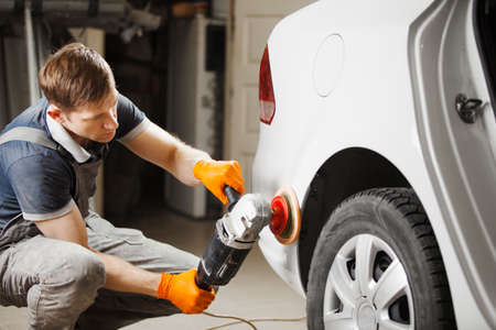 Worker cleaning white car with polishing and waxing, close-up. Auto repair shop. Car detailing. 版權商用圖片