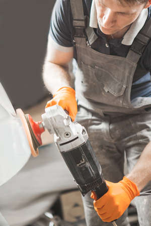 Worker with orbital polisher in auto repair shop. Car detailing. Final recovery of automobile.