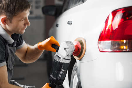 Car detailing series: polishing white vehicle in auto repair shop. Male worker recovers bodywork of automobile.