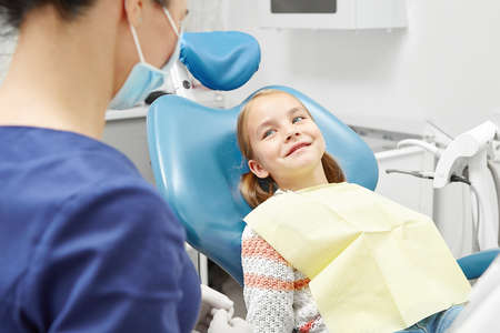 Female dentist with happy child at clinic. Pediatric dentistry. Young girl in doctor office.