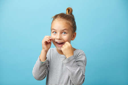 Portrait of smiling little five years old girl brushing her teeth with dental floss on blue isolated background.