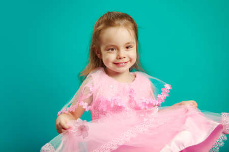 Image of beautiful child girl wears pink dress, holding it by the edges, cute posing, stands on blue isolated background. Three year old kid in female clothing.