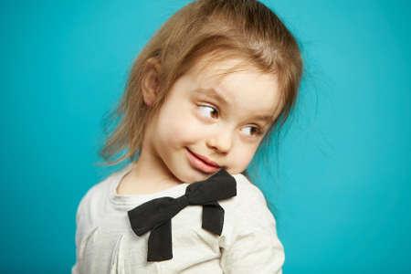 Little girl flirts, turns back, has a tricky facial expression, head leaned sideways, shows off flirtatiousness, coquet child. 版權商用圖片