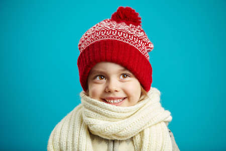 portrait of beautiful little girl in red winter hat on blue background, has big brown eyes, charmingly smiling, expresses joy and affection, baby cute image 版權商用圖片