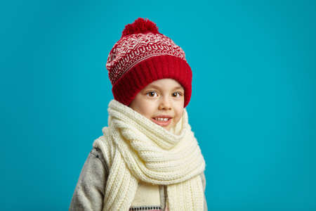portrait of cute little girl in winter red hat and scarf on blue background, has a serious face, expresses surprise and shock, emotional children shot