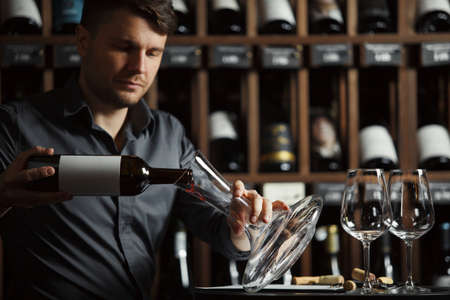 Serious sommelier pouring red wine from opened bottle in decanter designed to degustate and taste alcohol beverages, cellar full with containers collection having labels placed on shelves