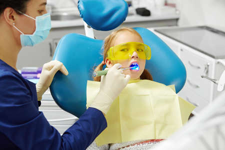 Pediatric stomatologist drying seal on teeth with led lighting, final stage of treatment. Little girl in dentist office.