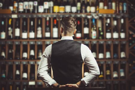 Bartender at wine cellar full of bottles with exquisite alcohol drinks that have various sweet and sour tastes and dates of manufacture on large wooden shelves.