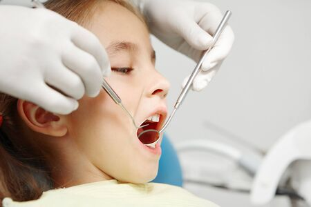 Close up shot of dentist examines of smiling child at the pediatric dentistry clinic. Happy little girl