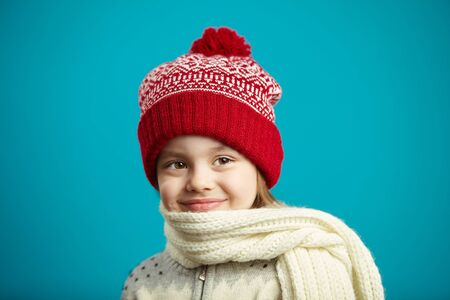 Close up portrait of little charming girl in red winter hat and wrapped scarf on blue background.