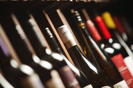 Wine cellar with elite drinks on shelves with names written on boards. Background with different expensive alcoholic beverages