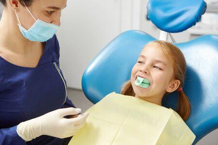 Kind probiert ein Mundstück an, um den Biss in der Zahnarztpraxis in der Kinderzahnheilkunde zu korrigieren. Standard-Bild