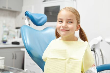 Happy five year old child sitting in the dentists office and smiling. Beautiful girl in the chair. 写真素材
