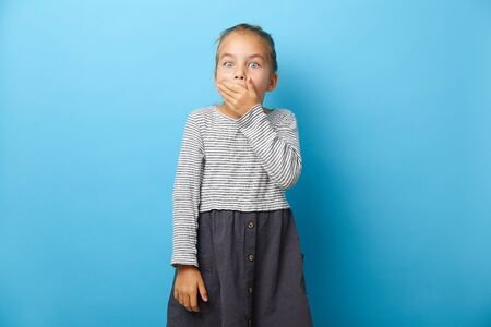 Funny little girl covers mouth with surprise, has a shocking expression on face, emotional portrait on blue isolated. 写真素材