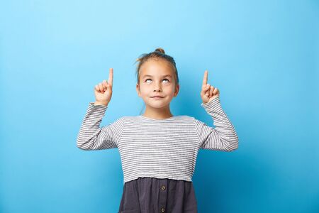 Surprised pretty little girl pointing with two fingers to up, looking to up, isolated on blue