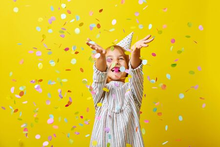 Cheerful little girl celebrates birthday. Child is standing in the rain of confetti.