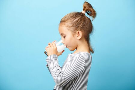 Child girl drinks milk without lactose, sideways portrait against blue isolated.