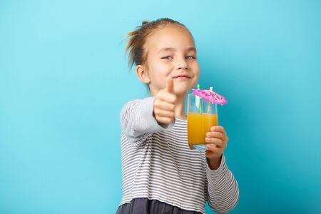 little child girl with orange juice, shows thumbs up, has a positive emotions, stands on blue backgound.