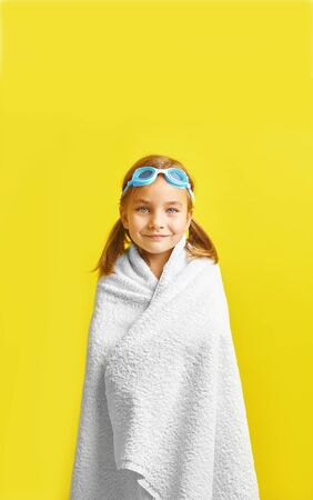 Vertical image of funny happy child in swimsuit and swimming glasses , wrapped in a towel, on colored background.