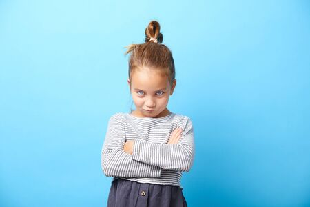 Offended little girl crosses her arms and makes a disgruntled expression of protest. Naughty child on blue isolated. Stock fotó