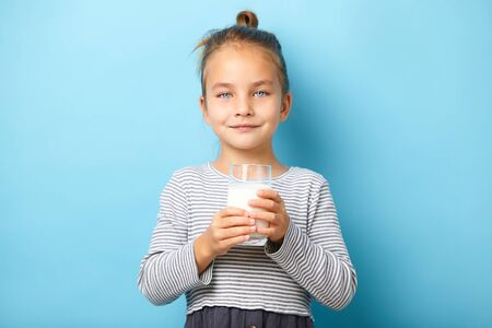 Cute little girl with glass of milk on blue isolated background. 写真素材