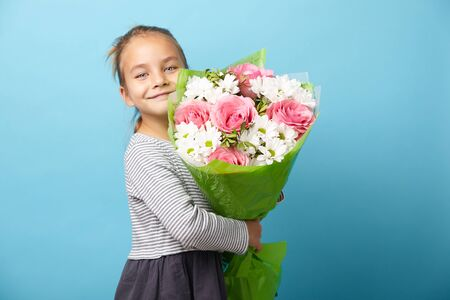 Smiling child girl with beautiful bouquet of flowers, portrait on blue isolated. 写真素材