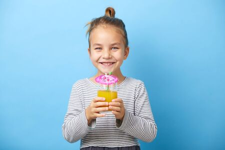 Caucasian child girl drinks orange juice and smiling. Banque d'images - 135526330