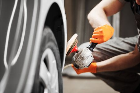 Polished white car. polishing machine for polish finishing. A man cleans the automobile from scratches. Banque d'images - 133242707