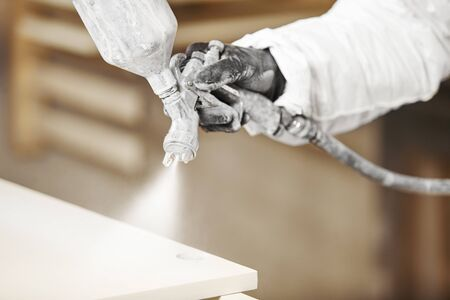 Close-up of industrial worker using paint gun or spray gun for applying paint, airless spraying. Banque d'images - 135526336