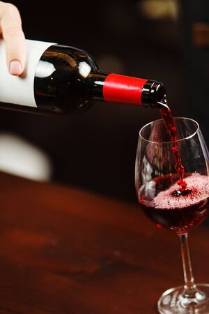 Waiter pouring red wine into wineglass. Sommelier or bartender pours alcoholic drink without splashes into glassware utensil Banque d'images - 133242674
