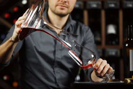 Sommelier pouring wine into glass from decanter. Male waiter pour out alcohol beverage into wineglass at bar counter. Bartender at work Banque d'images - 133236127