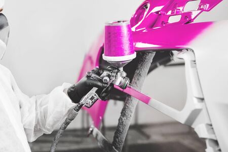 Auto mechanic worker painting car bumper with spray gun in a paint chamber during repair work. Banque d'images - 135526371