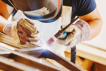 Male in face mask welds with argon-arc welding Banque d'images - 135526372