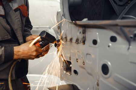 Cleaning of weld. Cleaning of weld. Processing of welding seams pneumatic grinding machine with an abrasive wheel. Repair and recovery of car bodywork. Stok Fotoğraf