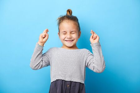 Joyful little girl clenches teeth, raises fingers crossed, makes desirable wish, squeezed her eyes shut, waits for good news, stands indoor over blue background.