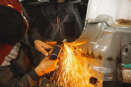 Processing of welding seams pneumatic grinding machine with an abrasive wheel. Cleaning of weld. Repair of car body. Banque d'images - 140370706