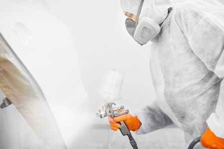 Spray painter worker in protective glove with airbrush pulverizer painting car body in white paint chamber.