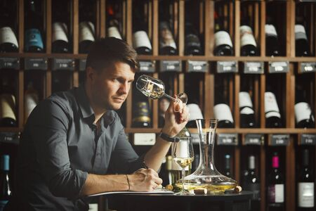 Man looking at wine glass with alcoholic drink Banque d'images - 140470598