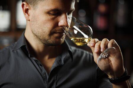 Bokal of white wine on background, male sommelier appreciating drink