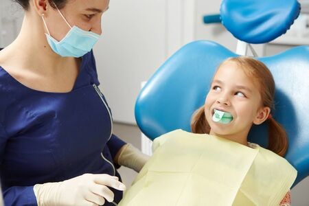 Pediatric dentist tries on the little girl a mouth guard for identifying and correcting the bite.