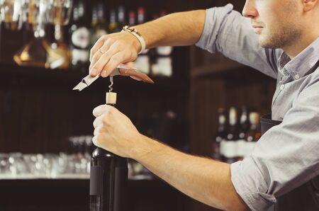 Bartender concentrated on uncork of elite drink at bar counter.