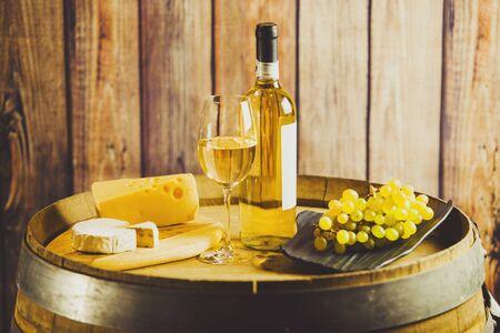 Weißwein auf Fass mit Trauben und Käse auf dem Hintergrund der Holzwand. Standard-Bild