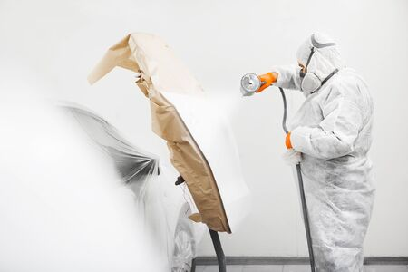 Auto mechanic worker painting a white car with spray gun in a paint chamber during repair work. Service for repair restoration of the car.