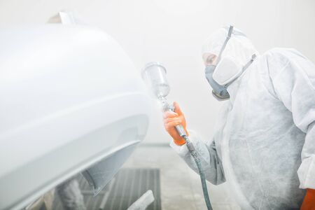 Male repairman painter in chamber painting automobile car elements. Worker paints the vehicle in white with a spray gun. Body repair cars. Banque d'images