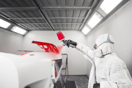 Man sprays white dye on the elements of the vehicle. Recovery of the car after the accident. High-level repair technology.