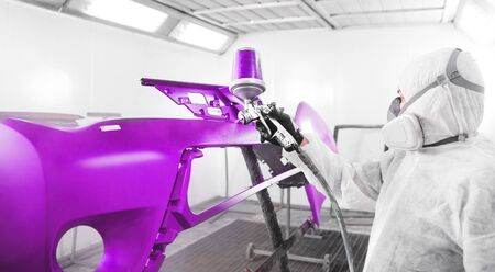 Worker spraying violet paint with spray gun on car bumper. Professional vehicle painting in a paint booth