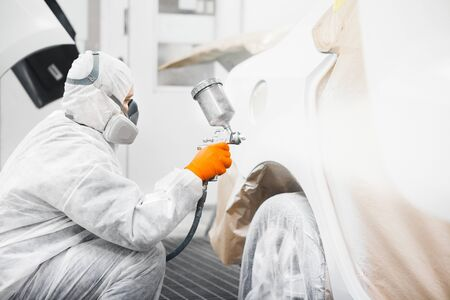 Automobile repairman painter in mask and protective workwear painting white car body in paint chamber. Restoration of vehicle after the accident.