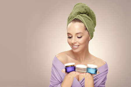 Happy woman with clean fresh skin hold a different of face care creams, wearing in bathrobe and towel on head. Cosmetology, beauty and spa. Concept of skin rejuvenation without surgery.