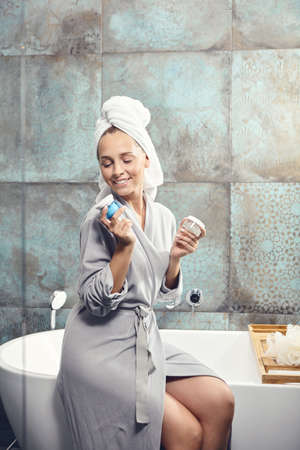 Woman in spa bathrobe sitting on bath, hold face cream and scrub in hand, smiling looks to camera.