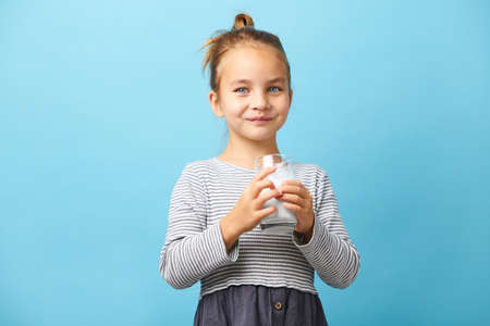 portrait of smiling child girl holding glass of milk on blue isolated.